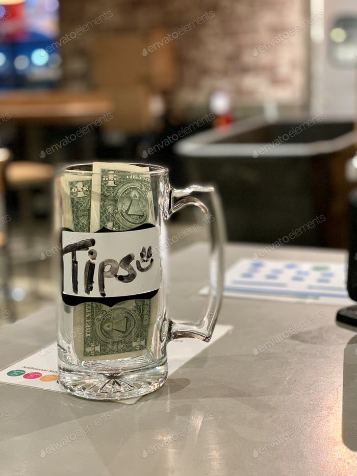 Tips glass jar at business next to cashier with money people leave as tips for workers back at work
