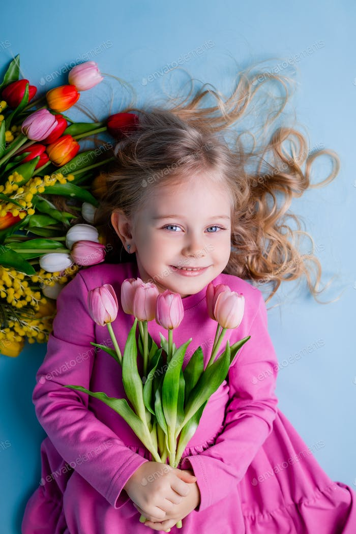 small blonde with blue eyes in a pink dress is lying next to a spring bouquet
