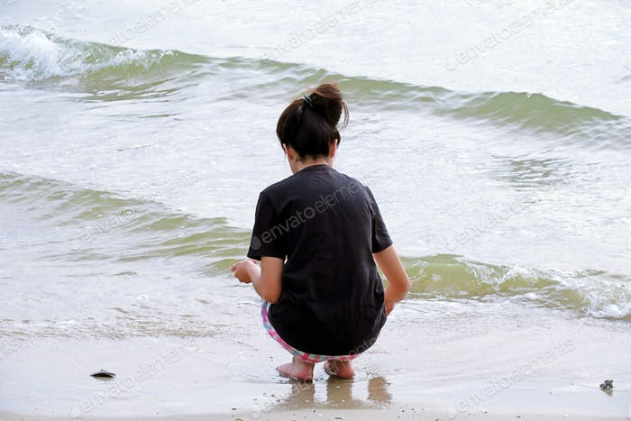 Young teenage girl sitting enjoy at the beach ocean