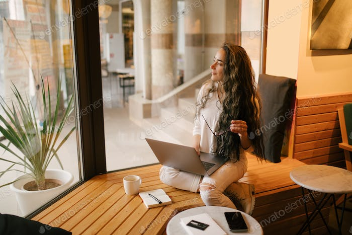 Young woman working online using her laptop and notebook, sitting in a coffeehouse, drinking coffee.