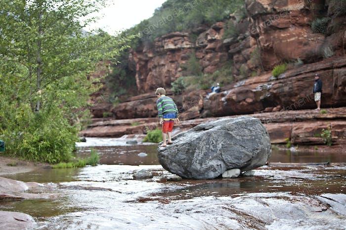 Niño en un suéter y traje de baño se aspira en el agua de un arroyo de la seguridad de una roca