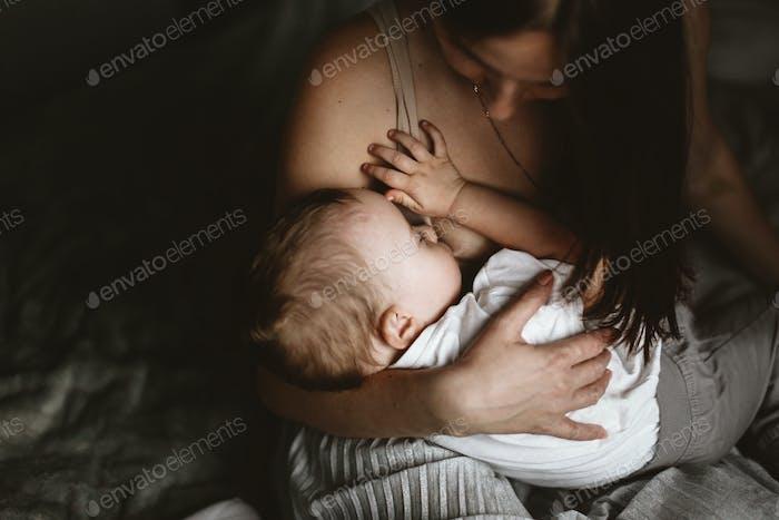 Мама брюнетка грудное вскармливание малыша. Концепция грудного вскармливания стиль жизни, коричневый тонизирование