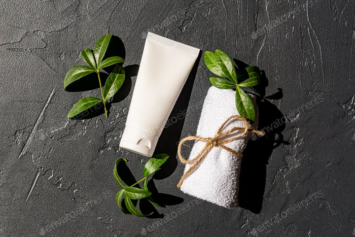 Close up of white unbranded white package of face or hand cream or facial mask with rolled towel