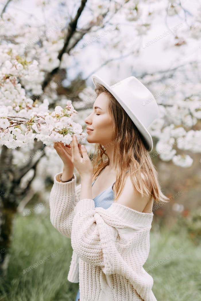 A young delicate woman in a silk dress and hat enjoys the smell of blooming flowers in the garden
