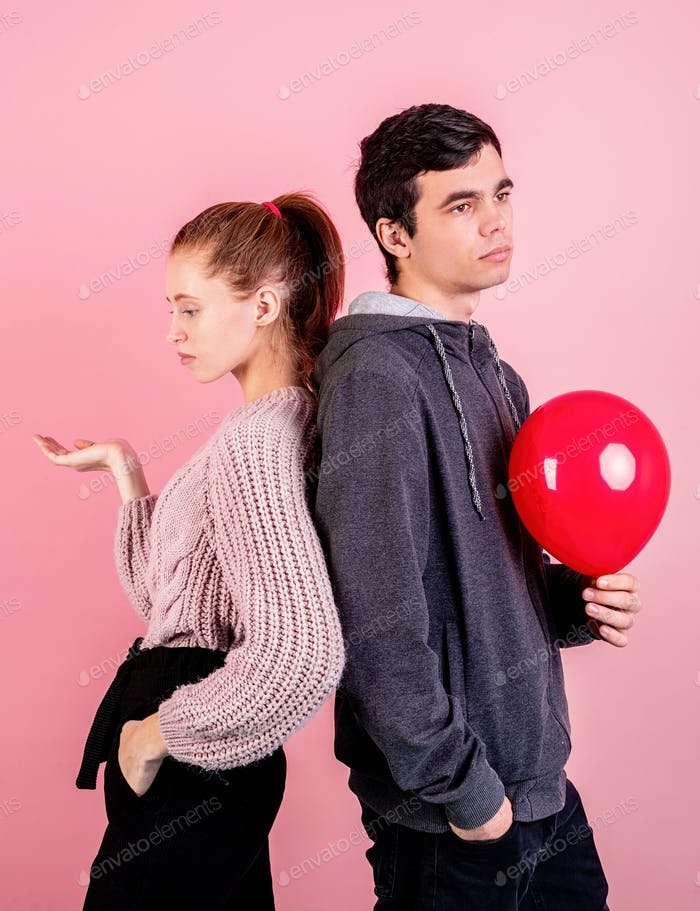 Young couple having problems or disagreement, standing back to back looking away on pink background