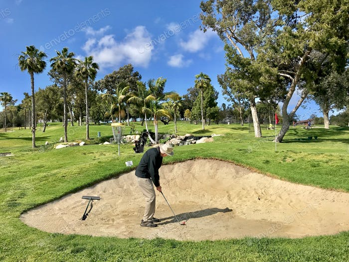 NOMINATED Active senior man getting ready to hit out of the sand trap on a beautiful 3 par golf