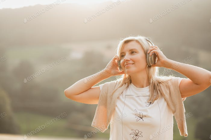 Young woman in her 30s listening to music with wireless headphones in forest. Copy space
