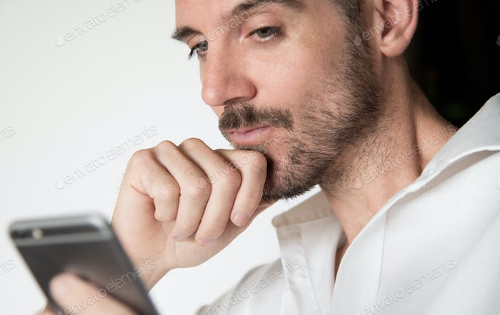 Male face reading smart phone with hand on chin