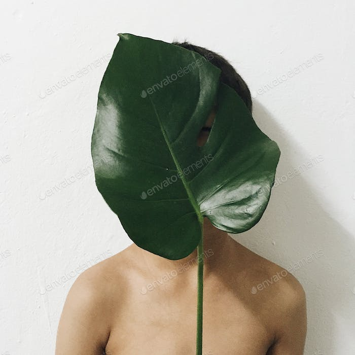 portrait picture of a boy holding monsterra leaf