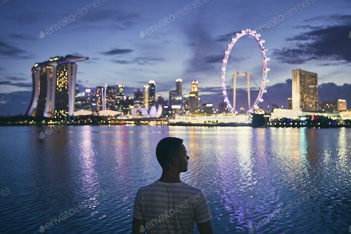 Singapore at dusk. Silhouette of lonely man against illuminated urban skyline.