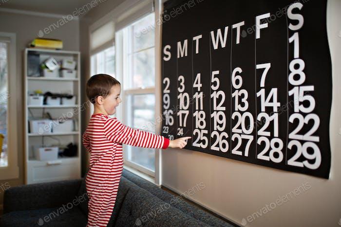 niño emocionado señalando al 25 de diciembre buscando emocionado por la mañana de Navidad