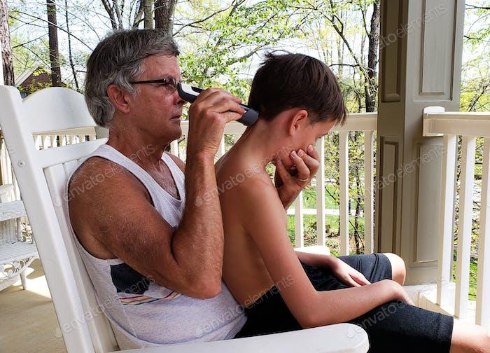 Grandpa is cutting grandsons hair during the coronavirus pandemic quarenteen and hoping he not look