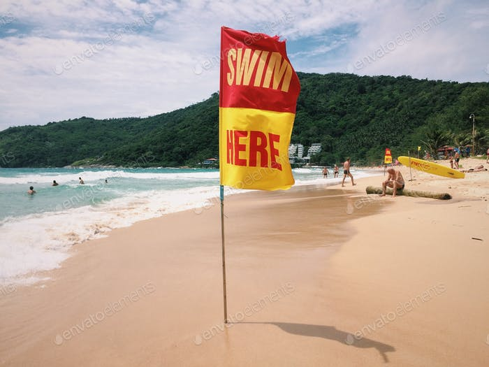 Warning yellow-red sign on the beach