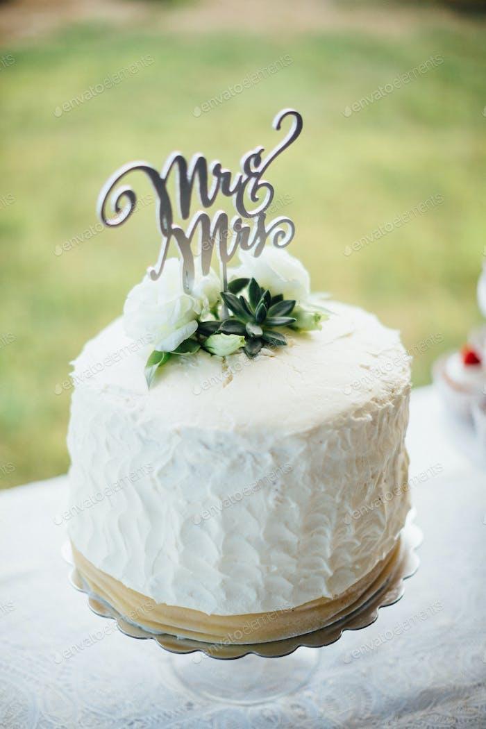 Herr und Frau Zeichen sitzt oben auf einer weißen Hochzeitstorte auf einer weißen Spitze in einem Sommer