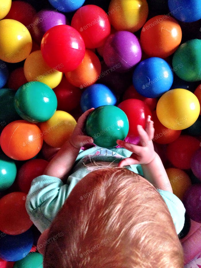 Baby playing in ball pit
