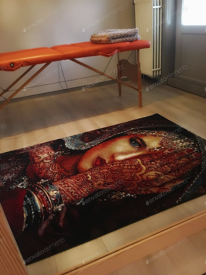 Massage table and a printed carpet