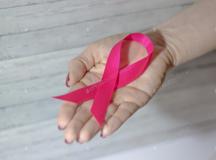 Woman hand giving satin pink ribbon