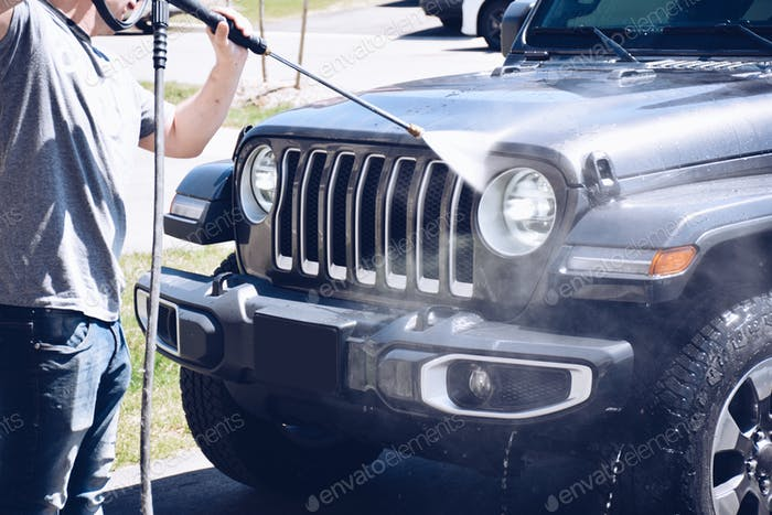 Man is washing a car with power washer