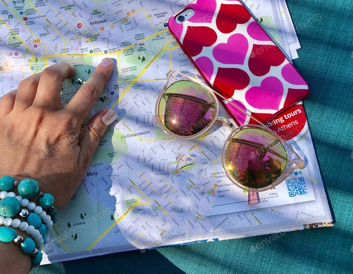 A woman's pretty hand showing a spot on a map with colorful sunglasses and cellular case.