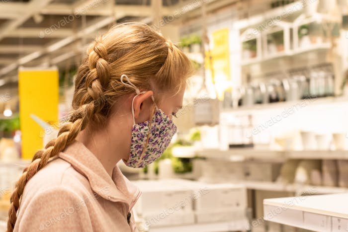 Girl wearing face mask at the department store. Covid-19 outbreak. Mandatory face masks