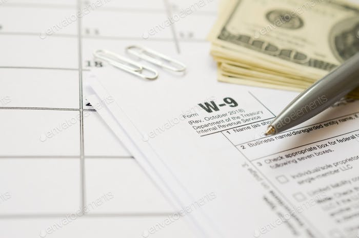IRS Form W-9 Request for taxpayer identification number and certification blank lies with pen and