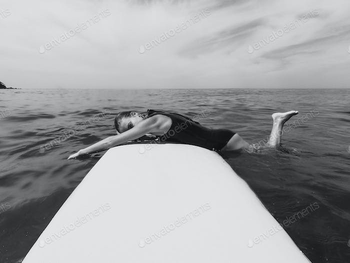 Woman laying on the surfboard