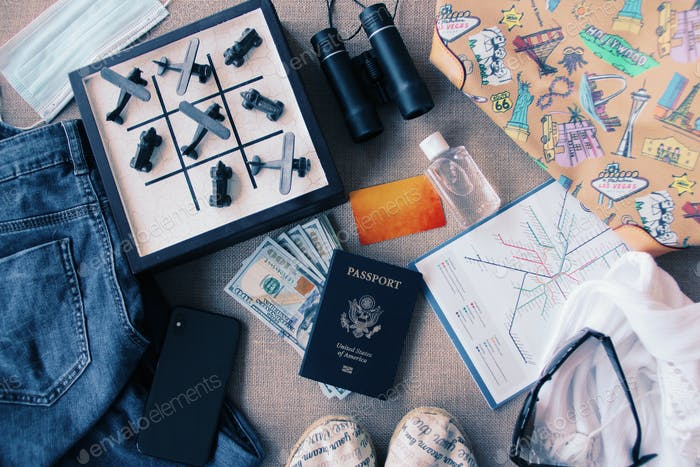 Travel essentials flat lay with a tic tac toe game with airplane & car pieces where the planes won