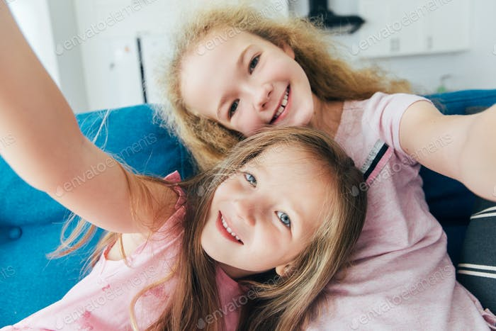 Self portrait of crazy, foolish sisters, laughing, together making selfie on mobile phone or camera