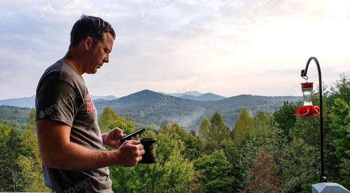 Active millenial drinking his first cup of coffee early morning in the mountains while checking his