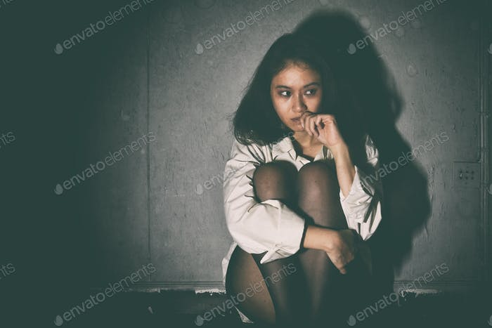 Depressed and frustrated, Sad woman sitting in the dark room, Mental health concept.