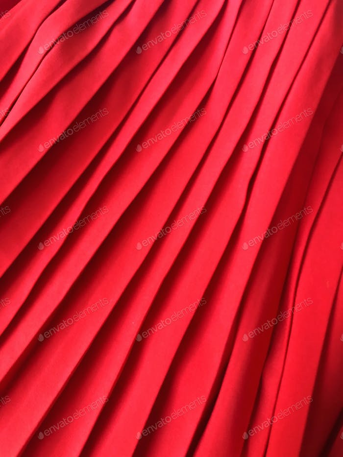 Bright red pleated pleats folds of silky fabric.