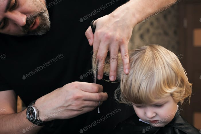 A little blonde boy is trimmed in the barbershop. Bright emotions on the face, facial expression. N