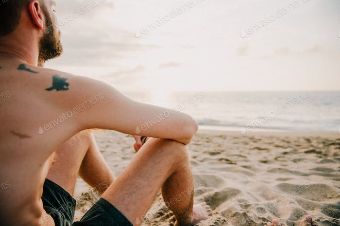 Guy sitting on the beach looking at ocean