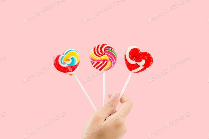 Woman hand holding colorful lollipops isolated on pastel pink background with clipping path.