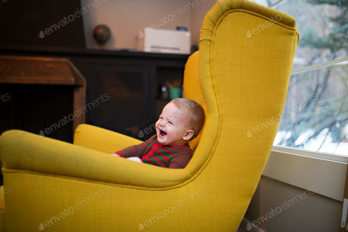 happy toddler laughing in a yellow chair