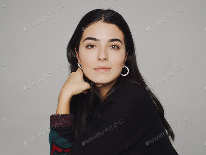 Portrait of eastern black-haired woman in black sweater on the grey background
