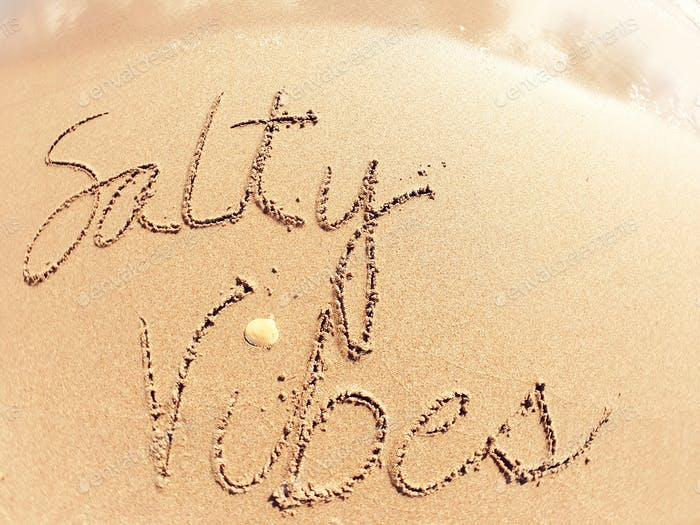 Salty Vibes written on the sand
