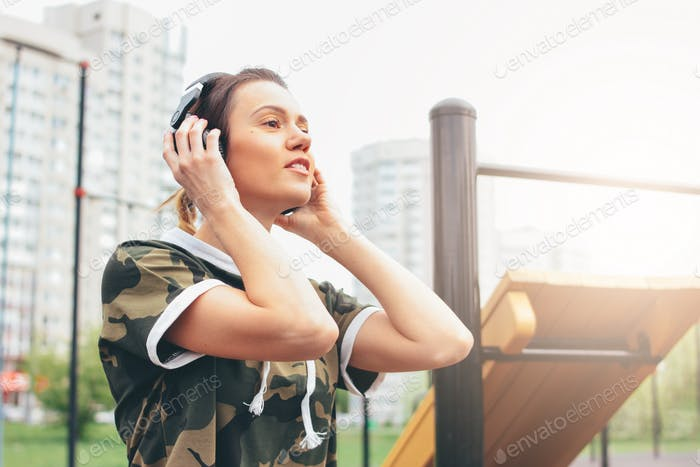 Attractive fit young woman in headphones and military colored sport wear rest on the street workout
