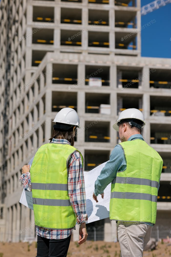 ire and technical safety engineers at the construction site inspect the multi-storey building