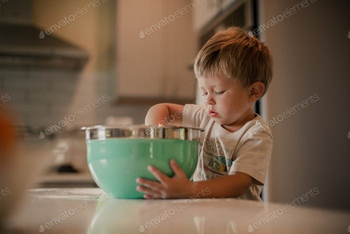 Toddler boy focusing on stirring his summer snack in a big turquoise bowl - natural light candid