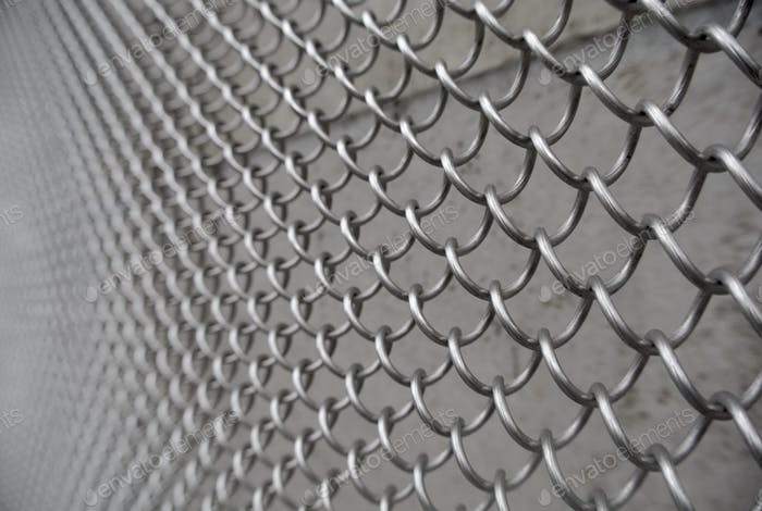 Mit  Kette verbundener Zaun vor einer Mauer.
