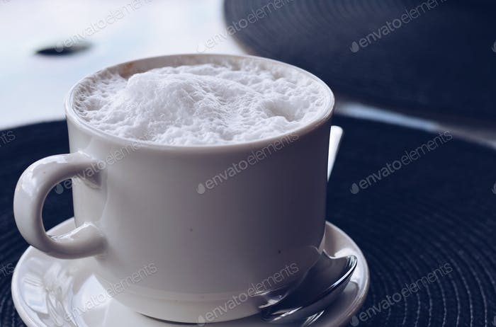 A simple white cup with cappuccino on a placemat at a cafe restaurant