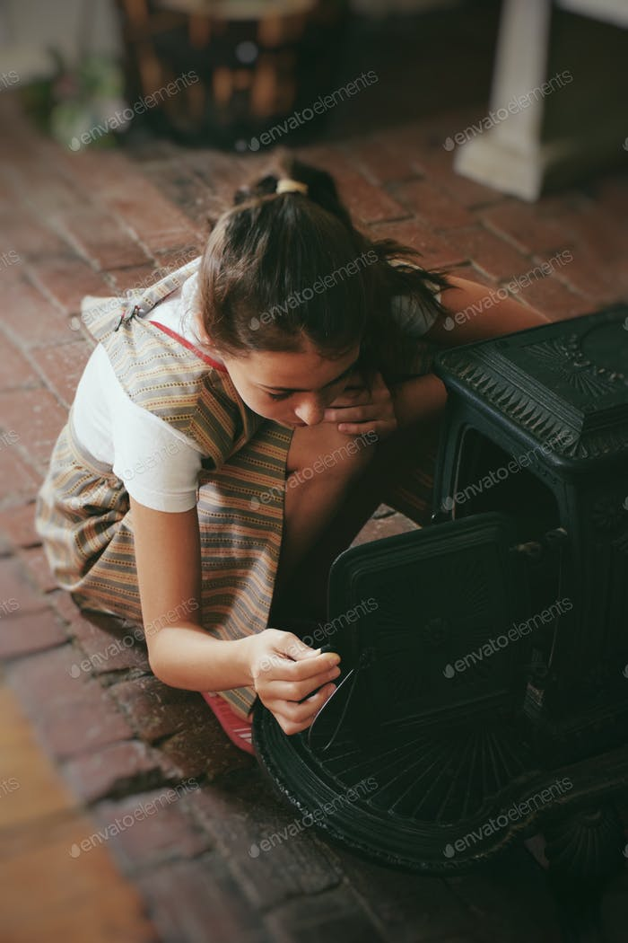 Girl looking into an old fashioned pioneer oven 💲