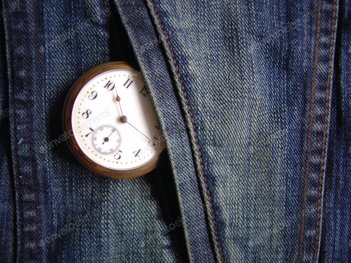 Time, the power of time. Blue weathered Denim & gold vintage watch, conceptual, background
