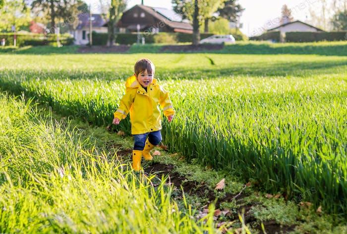 Glücklicher kleiner lächelnder Junge in leuchtend gelbem Regenmantel und Gummistiefel läuft durch das Feld mit