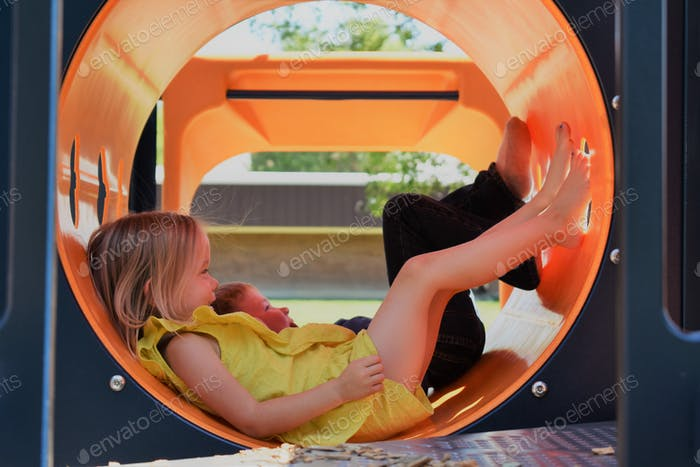 Two toddlers playing in a tube at a park in the summer, boy and girl smiling at a playground.