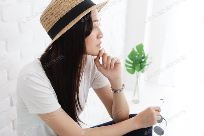 Woman thinking in white room.