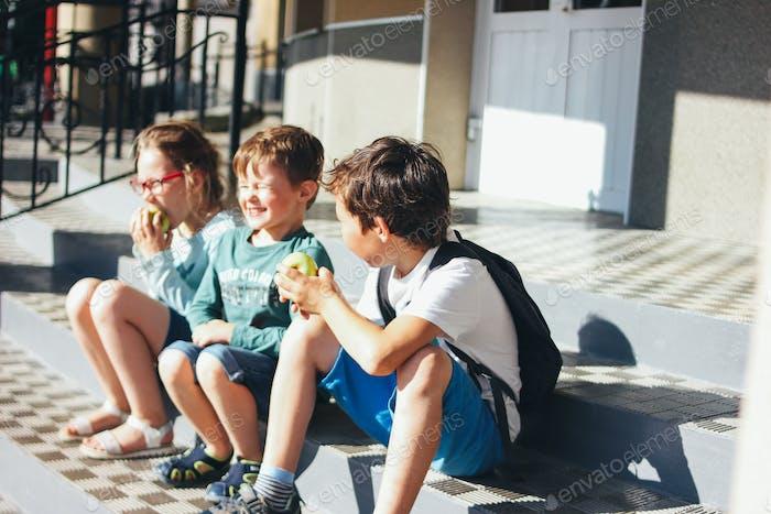 Three children tweens friends having fun near school
