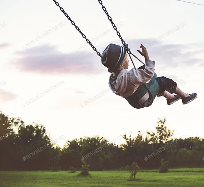 Young boy in a top hat swinging