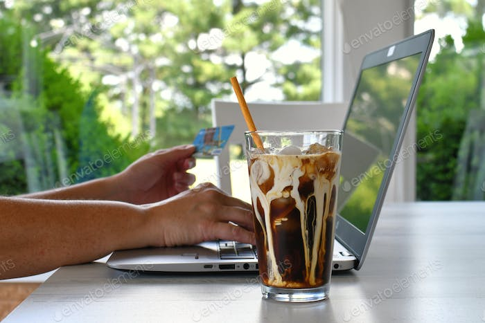 woman on laptop with an iced coffee latte cream swirl credit card in hand for online shopping
